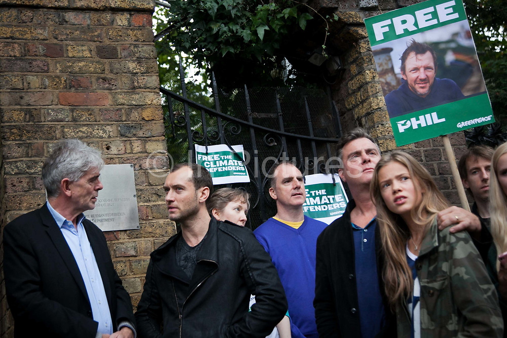 Jude Law, actor, and John Sauven, Director of Greenpeace in conversation outside the Russian Embassy. Greenpeace and sympathisers picket  the Russian Embassy in London as part of a global day of action in defence of the 30 Greenpeace activists arrested and detained in Russia. All 28 activists and the 2 journalists are now chrged with piracy after a week of detainment in a Murmansk prison. Gazprom, with it's appaling health and safety record is about to start drilling in the Arctic as one of the first big oil companies. The Arctic 30 were arrested and the ship the Arctic Sunrise ceased by armed Ruassian special forces in international waters in the Arctic after Greenpeace peacefully tried to scale a Gazprom oil rig to prevent it from drilling for oil in the highly sensitive arctic sea.