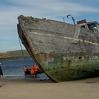 Tourists load into a zodiac raft beside a decaying old ship on a beach at New Island, in Britain's Falkland Islands.