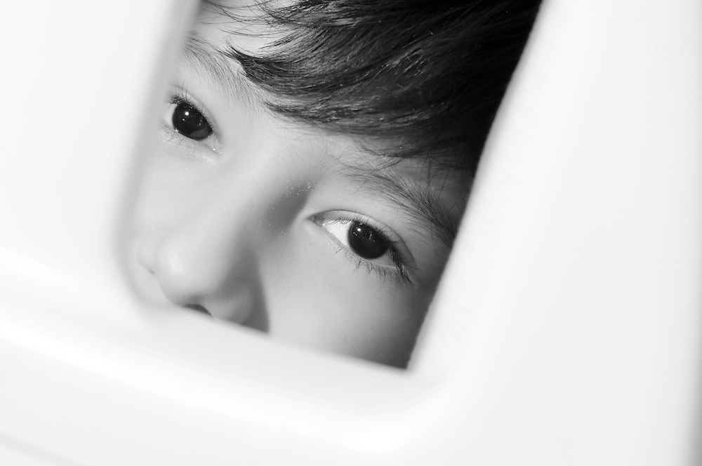 A little boy looks through the handrail of his hospital bed during a Flashes of Hope photo shoot at the Boston Children's Hospital.