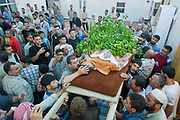 Men are gathered in a local mosque to pray for their loved one during a burial ceremony of a young man who had allegedly been shot by a Syrian government sniper during his journey in Aleppo on Sunday, June 10, 2012. (Photo by Vudi Xhymshiti)