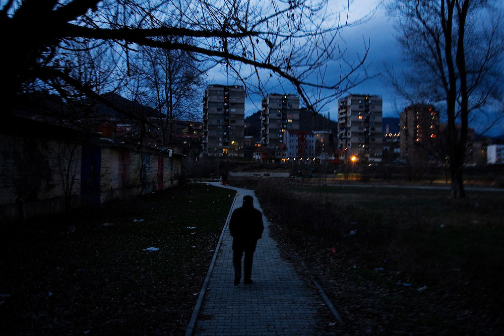 An Albanian man walks through a park on the south side of the Ibar river toward an ethnically mixed enclave on the north side where many Albanians still live.<br /> <br /> Mitrovica, Kosovo - One-year anniverary of Independence - February 17, 2009.