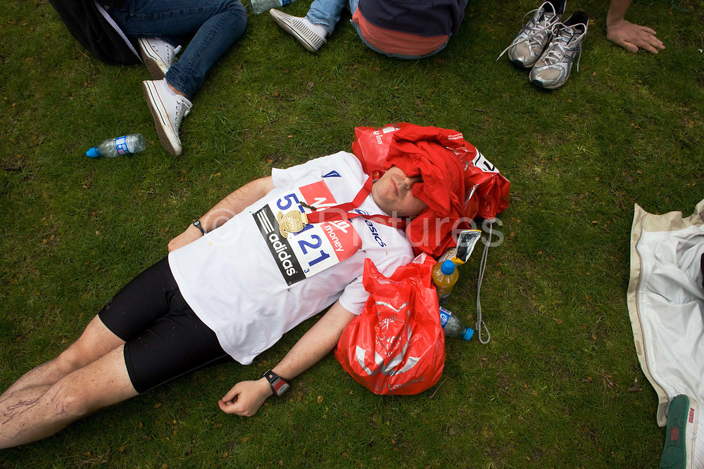 With his face covered and a well-earned medal around his neck, a male London Marathon runner has collapsed on grass after completing a gruelling 26 miles 385 yards through the capital's streets, before being met by family. With the few possessions around him - bottles of sponsored Lucozade isotonic drinks and clothing bags - he lies motionless with other competitors and spectators around him