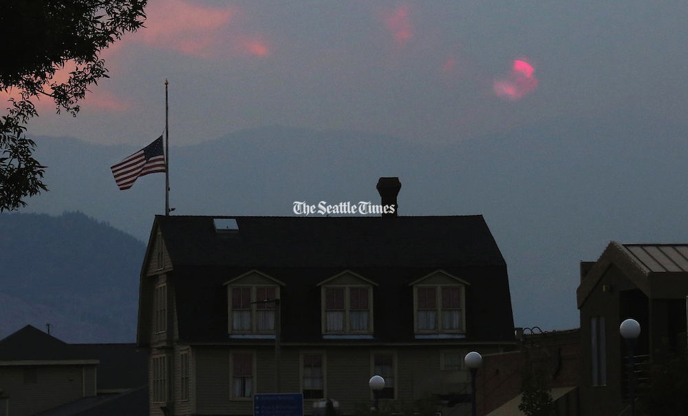 Honoring the three firefighters lost to the Washington State wildfires, a flag flies at half-staff as smoke from wildfires obscures the setting sun seen from downtown Chelan. <br /> The flag is above Campbell House, part of the Campbell's Resort on Lake Chelan. Friday August 21, 2015<br /> <br /> Alan Berner / The Seattle Times