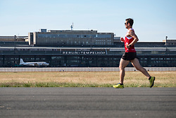 Runner on runway at former Tempelhof Airport now public park  in Kreuzberg, Berlin, Germany