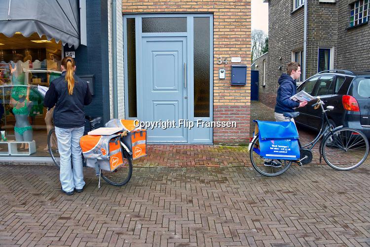 Nederland, Born, 1-3-2018Een postbezorger van Postnl en Sandd passeren elkaar tijdens hun ronde om poststukken te bezorgen.Foto: Flip Franssen