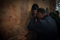14 April 2019, Jerusalem: People close their eyes to pray at the Holy Tomb during Palm Sunday service at the Church of the Holy Sepulchre, in the Old City of Jerusalem.