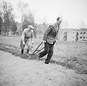Two men working a small plough by hand in filed near houisng Finland 1950s