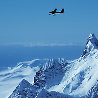 """A Twin Otter ski plane flies over Calley Glacier, and a crag called """"Wiltsie's Peak"""" on the Antarctic Peninsula.  Gerlache Strait is in the background"""