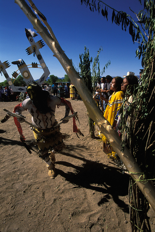 A Mountain Spirit (Gaan) or Crown Dancer dances inside a ceremonial tepee and in front of an Apache girl during her Sunrise Dance, on the San Carlos Apache Indian Reservation in Arizona, USA. The Sunrise Dance, the first menstruation rite of an Apache girl, is held during the summer, within one year after the girl has had her first menstruation, and lasts for four days. The ceremony is an enactment of the Apache creation myth and during the rites the girl 'becomes' Changing Woman, a mythical female figure, and comes into possession of her healing powers. The rites are supposed to prepare the girl for adulthood and to give her a long and healthy life without material wants.