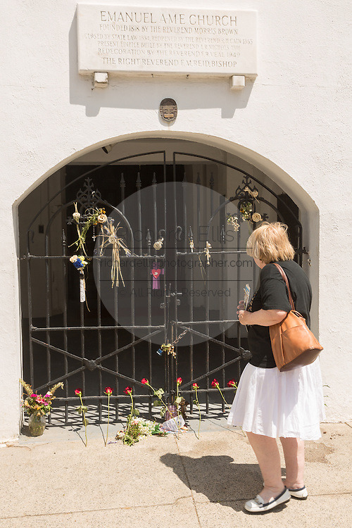 A woman pauses at the historic Mother Emanuel African Methodist Episcopal Church on the eve of the anniversary of the mass shooting June 16, 2016 in Charleston, South Carolina. Nine members were gunned down during bible study at the church on June 17, 2015.