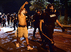 A protestor walks with his right arm raised with Charlotte-Mecklenburg police officers along Old Concord Rd. on Tuesday night, Sept. 20, 2016 in Charlotte, N.C. The protest began on Old Concord Road at Bonnie Lane, where a Charlotte-Mecklenburg police officer fatally shot a man in the parking lot of The Village at College Downs apartment complex Tuesday afternoon. The man who died was identified late Tuesday as Keith Scott, 43, and the officer who fired the fatal shot was CMPD Officer Brentley Vinson. Photo by Jeff Siner/Charlotte Observer/TNS/ABACAPRESS.COM