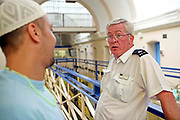 A prison officer talks to one of the inmates on D wing landing. HMP Wandsworth, London, United Kingdom.