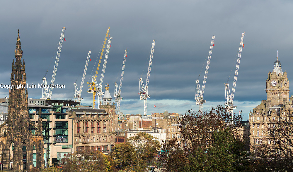 construction site tower cranes  at the large St James Centre redevelopment construction site. Cranes are free to turn with the wind and are seen lined up in a row against the skyline of the city.