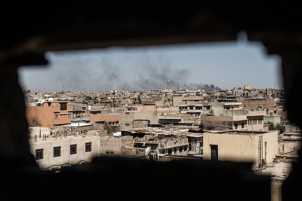Neighborhoods that ISIS still occupies can be seen through a small hole where Iraqi Federal Police's snipers take up a position in West Mosul, Iraq. Nuri al-Kabir Mosque is seen in the distance. It is the place at which Islamic State's supreme leader Abu Bakr al-Baghdadi gave his famous sermon in 2014 declaring the establishment of the group's rule in Iraq and neighboring Syria.<br /> <br /> イラク警察軍スナイパーの陣地からISISが支配するエリアを覗く。遠くには2014年にISISのリーダー、アブ・バクル・アル・バグダディがいわゆる「イスラム国」の建国とカリフへの即位を宣言したアル・ヌーリモスクが見える。モスル西部、イラク2017年撮影。