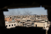 Neighborhoods that ISIS still occupies can be seen through a small hole where Iraqi Federal Police's snipers take up a position in West Mosul, Iraq. Nuri al-Kabir Mosque is seen in the distance. It is the place at which Islamic State's supreme leader Abu Bakr al-Baghdadi gave his famous sermon in 2014 declaring the establishment of the group's rule in Iraq and neighboring Syria.<br />
