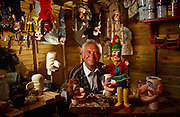 One man is acclaimed the world over and is synonymous with making hand-carved puppets - Bryan Clarke. He is Chairman of the British Punch & Judy Fellowship and has been a professional Punch & Judy man for well over 50 years, making and supplying puppets from his workshop near Lowestoft on the east coast of England for the last 30 years. Hundreds of Punch & Judy performers throughout the UK and overseas use Bryan's puppets and some are seen here in various stages of production - some finished and hanging from this shed roof while in front of this talented artist, we see blocks of wood still being shaped into the familiar characters that children the world over recognise as Mr Punch and other figures. Mr Clarke smiles at the view in this relaxed portrait taken in 1992.