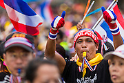 """15 NOVEMBER 2013 - BANGKOK, THAILAND: An anti-government protester blows a whistle and gives a thumbs up to protest leaders in Bangkok. Tens of thousands of Thais packed the area around Democracy Monument in the old part of Bangkok Friday night to protest against efforts by the ruling Pheu Thai party to pass an amnesty bill that could lead to the return of former Prime Minister Thaksin Shinawatra. Protest leader and former Deputy Prime Minister Suthep Thaugsuban announced an all-out drive to eradicate the """"Thaksin regime."""" The protest Friday was the biggest since the amnesty bill issue percolated back into the public consciousness. The anti-government protesters have vowed to continue their protests even though the Thai Senate voted down the bill, thus killing it for at least six months.     PHOTO BY JACK KURTZ"""