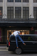 A driver stands on the rear wheel of his vehicle and reaches to polish its roof, in a central London street, England.