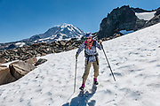 Caution: the unmaintained and unmarked Knapsack Pass trail exposes experienced hikers to slippery scree and steep snow (possibly icy), best hiked in late summer using a good GPS device, map, and trekking poles. Mount Rainier rises to 14,411 feet elevation, seen here from the headwaters of Cataract Creek in Mist Park, along the Spray Park–Knapsack Pass Loop trail, in Mount Rainier National Park, Washington, USA.