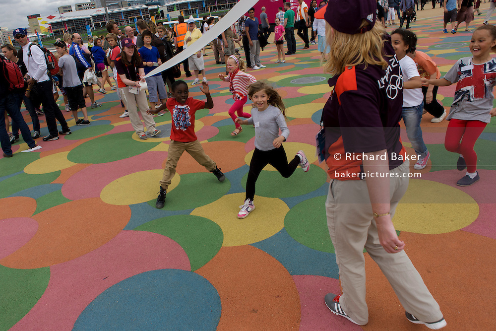 Children practice winning a sprint final on the grid-like patterned floor in the Olympic Park during the London 2012 Olympics. The kids race under a pretend track tape held by two volunteer Games Makers who offer the everyone winners' chocolate gold medals. This land was transformed to become a 2.5 Sq Km sporting complex, once industrial businesses and now the venue of eight venues including the main arena, Aquatics Centre and Velodrome plus the athletes' Olympic Village. After the Olympics, the park is to be known as Queen Elizabeth Olympic Park. .