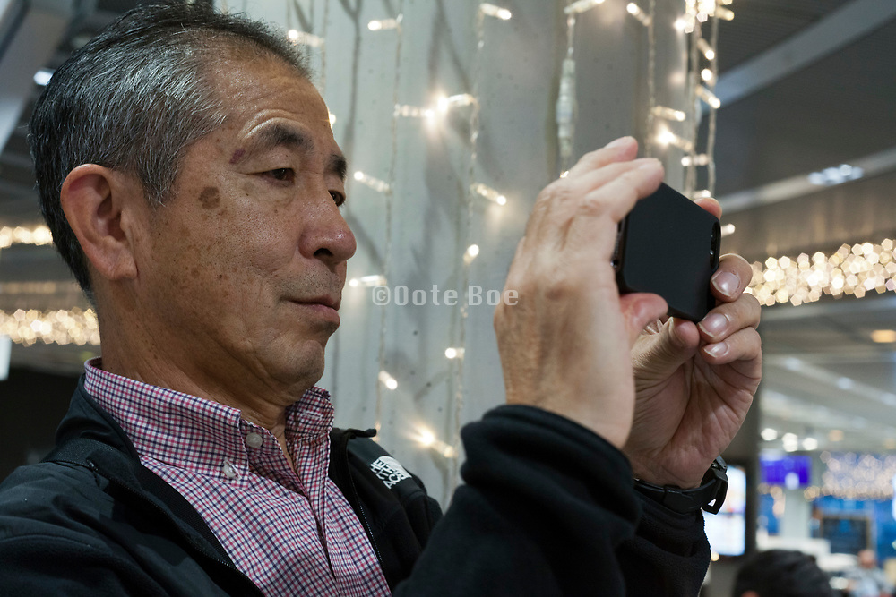 portrait of man photographing with a smartphone