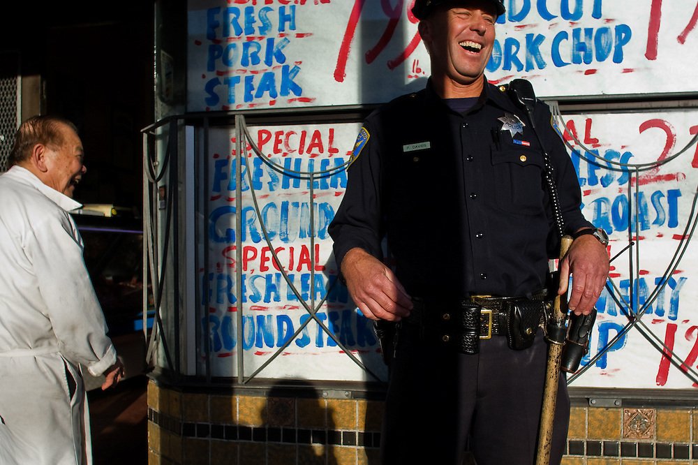 """SFPD Officer Paul Davies (right) shares a laugh with Bing """"Choy"""" Wilson, owner of Divisidero Meat Market, on February 13, 2007.  The San Francisco Police Department had recently increased foot patrol due to a rise in violent incidents between local gangs."""