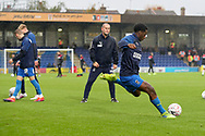 AFC Wimbledon attacker Zach Robinson (29) warming up and shooting at goal whilst being watched by AFC Wimbledon coach Mark Robinson during the The FA Cup match between AFC Wimbledon and Doncaster Rovers at the Cherry Red Records Stadium, Kingston, England on 9 November 2019.