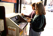 Tongan American sisters age 15 and 17 withdraw cash from machine in grocery.  St Paul Minnesota USA