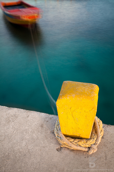 A fine art photograph of a bright yellow, single dock support, knotted with rope, attached to a colorful motion blurred boat in the Caribbean Sea.