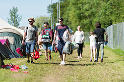 © Licensed to London News Pictures. 13/06/2014. Isle of Wight, UK.   Festival goers carry their bags and tents in a campsite Isle of Wight Festival 2014 in the early morning sun - today is expected to be the hottest day of the year in the UK.  .   The Isle of Wight festival is an annual music festival that takes place on the Isle of Wight. Photo credit : Richard Isaac/LNP