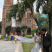 A bride and groom pose for pictures after their wedding at The Notre Dame Cathedral, Ho Chi Minh City, Vietnam. 3rd March 2012. Photo Tim Clayton