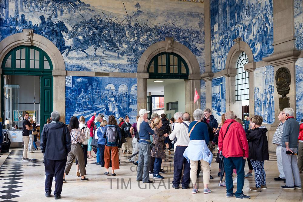 Tourists admire azulejos traditional Portuguese blue and white wall tiles Sao Bento railway station in Porto, Portugal