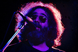 Jerry Garcia with The Grateful Dead Live at Huntington West Virginia 16 April 1978. A tight shot of Jerry looking upwards, singing into the mic. Halo of light in his hair.