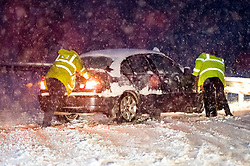 © Licensed to London News Pictures. 10/12/2017. Bourne End, UK. Police officers attempt to rescue a car which has spun on the road in heavy snowfall on the A41 near Bourne End in Buckinghamshire as parts of the south east of England are blanketed with snow for the first time this winter. Photo credit: Ben Cawthra/LNP
