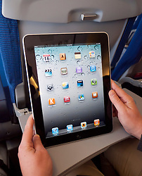 Woman using iPad computer tablet on passenger aircraft