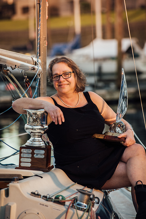 Portrait of sailor Carisa Bohus with SYSCO & OWSA trophies on her sailboar