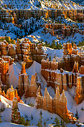 Hoodoos at Bryce Canyon's Sunset Point during winter. Bryce Canyon National Park, a sprawling reserve in southern Utah, is known for crimson-colored hoodoos, which are spire-shaped rock formations. The park's main road leads past the expansive Bryce Amphitheater, a hoodoo-filled depression lying below the Rim Trail hiking path. It has overlooks at Sunrise Point, Sunset Point, Inspiration Point and Bryce Point. Prime viewing times are around sunup and sundown.