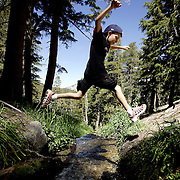 MAMMOTH, CA, AUG 22, 2006:  A young boy leaps over Coldwater Canyon Creek that leads into Emerald Lake while hiking in Mammoth, California  on August 22, 2006  (Photograph by Todd Bigelow/Aurora).