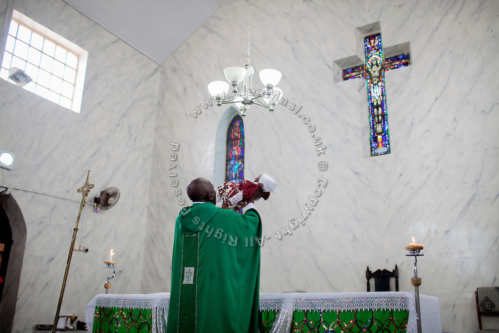 Priest Norbert Gokum, 40, is blessing a newborn child while celebrating a Mass Service at Saint Theresa's Christian Catholic Church in Jos, Plateau State, Nigeria. Saint Theresa's is the first Christian Catholic Church built in Jos, in 1923.