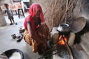 Rajasthani woman cooking over a wood fire. Combustible energy is sometime expensive on scarce resources..Barefoot College Tilonia, started by Bunker Roy in the 1970s. An organisation based upon creating economic self-empowerment and sustainable development initiatives, and self-sufficiency, for communities in the rural desert of Rajasthan, India. Energy autonomy with solar power capacitors, parabolic mirrors for cooking, solar powered water heating, and battery lanterns. Freshwater and irrigation through wells and desalination. A multitude of other economic initiatives run by grassroots Indian people, mainly women, where those who participate in, run the projects themselves. Many of them local lower castes, some physically handicapped, most with no paper qualifications, with support from others who gave up high flying money-making careers to be involved in working with poor rural communities. Mico-industries include solar lanterns, electric circuitry and lighting, crafts, textiles, children's toys, and sanitary towels. Also much emphasis on local and oral communications, radio, and puppetry. Now recognised internationally providing an educational resource most often directed towards communities of rural women worldwide.