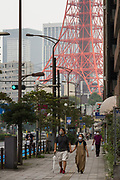 People wearing face masks against COVID-19 walk along a street in Tokyo with Tokyo Tower behind. Minato Ward, Tokyo, Japan. Sunday September 12th 2021