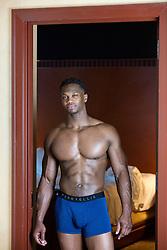muscular  black man in briefs standing in a bedroom doorway