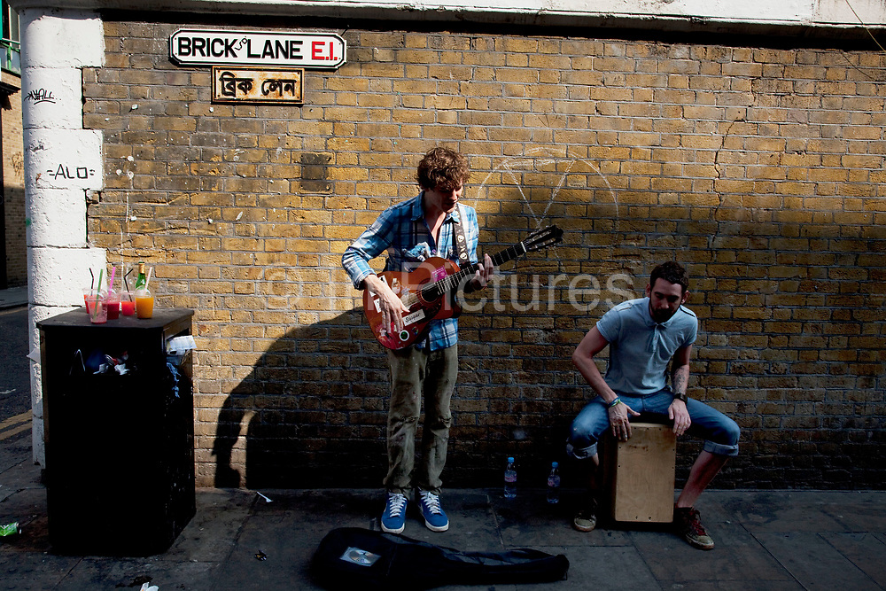 Brick Lane Market scenes along this most famous of East End markets in London. Musicians busking underneath the famous street sign. Brick Lane Market lunch time along this most famous of East End markets in London. Brick Lane Market is a London market centred around Brick Lane, Tower Hamlets. It is located at the northern end of Brick Lane and along Cheshire Street in east London. It operates every Sunday from around 8am to 2pm.