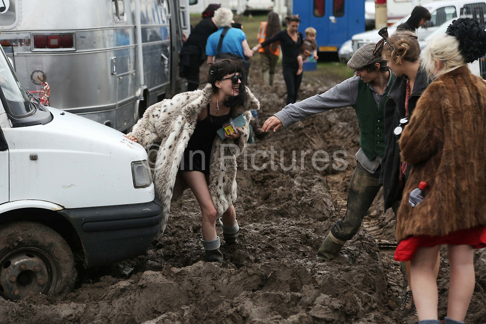 Heavy rain creates the familiar muddy base as festival goers arrive at the Glastonbury Festival in Glastonbury, United Kingdom. Glastonbury Festival is a five-day festival of contemporary performing arts that takes place near Pilton, Somerset. In addition to contemporary music, the festival hosts many other arts. (photo by Kristian Buus/In PIctures via Getty Images)