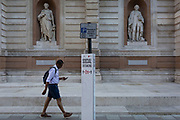 With a further 154 covid deaths reported in the last 24hrs, bringing the total to 43,081 in the UK during the Coronavirus pandemic, a man walks towards a social distance notice, attached to a parking sign pole outside the rear entrance of the Royal Academy in Burlington Gardens, whose statues to Georges Cuvier and Carl Linnaeus appear to be practicing correct lockdown rules, on 24th June 2020, in London, England.