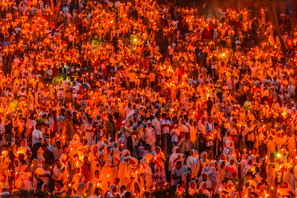 An entire hillside of people holding candles during a celebration of Meskel (an annual religious holiday of the Ethiopian Orthodox Church) which commemorates the discovery of the True Cross by the Roman Empress Helena in the fourth century. Meskel includes the burning of a large bonfire, or Demera. Arba Minch, Ethiopia.