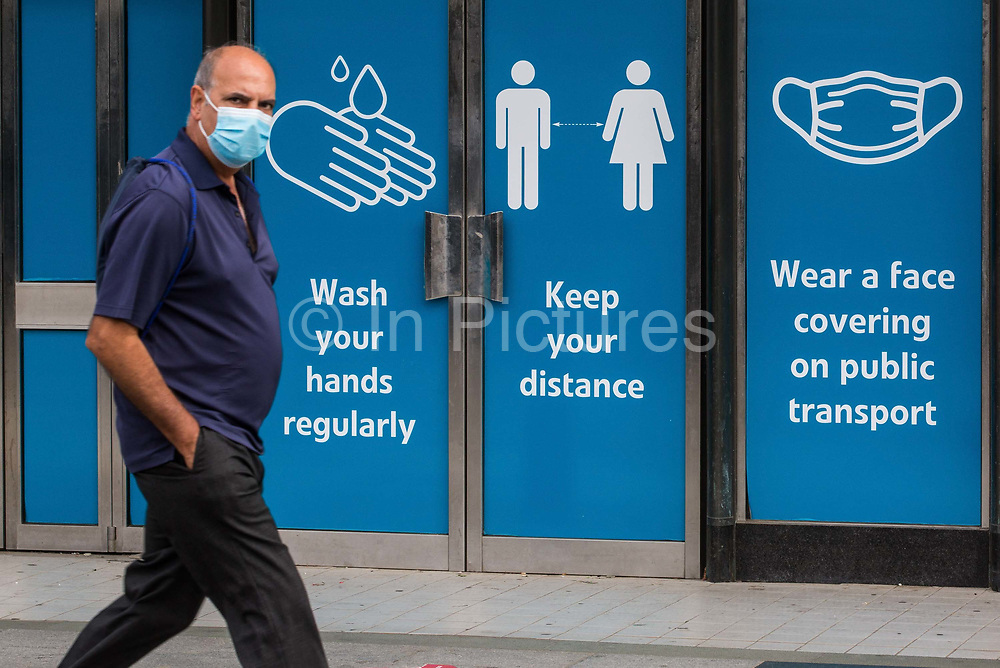 A member of the public passes COVID-19 public information displays on 9 September 2020 in Slough, United Kingdom. The UK government will implement tighter restrictions on social gatherings with effect from 14th September amid mounting concern regarding the possibility of a second coronavirus peak following a significant rise in the rolling seven-day national average of the number of cases reported.