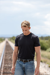 man walking on a railroad track