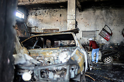 A man checks a burnt vehicle at a Nigerian-owned garage in Johannesburg Town, South Africa, on April 17, 2015. South African police on Friday fired rubber bullets to disperse rioters in central Johannesburg, a fresh hotbed of xenophobia violence. The current spate of xenophobic violence mainly affects Durban and Johannesburg. According to official figures, five people have been killed and thousands of immigrants displaced. EXPA Pictures © 2015, PhotoCredit: EXPA/ Photoshot/ Zhai Jianlan<br /> <br /> *****ATTENTION - for AUT, SLO, CRO, SRB, BIH, MAZ only*****