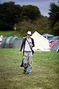 A man carries his drink through a field at  the Standon Calling Festival in Hertfordshire, UK.<br /> Standon Calling is a small independent festival set among the hills in Herfordshire that showcases World Music, Indie Music and dance Music. It is one of the new, small and quirky boutique festivals which have become popular in the UK.